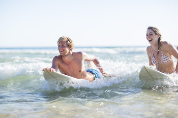 Happy young couple lying on surfboards in the sea