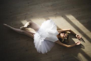 Ballerina in a tutu lying on the floor