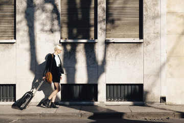 Blond woman with luggage walking on a pavement