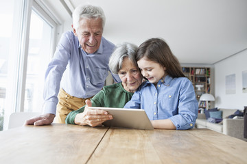Grandparents and their granddaughter looking at digital tablet at home