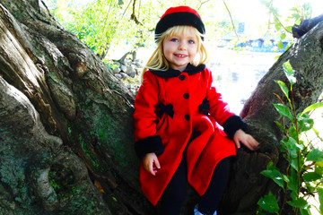 adorable toddler girl sitting on tree in red coat during holiday season