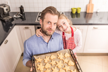 Father and daughter holding tray with homemade cookies