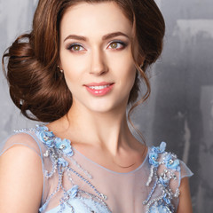 Close-up portrait of beautiful young woman in luxury dress, pastel color. Beauty fashion portrait