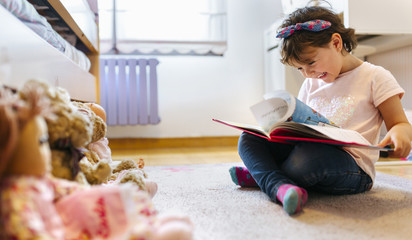 Laughing little girl sitting on the floor watching picture book