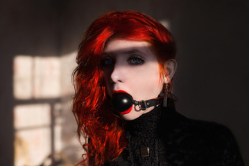 red-haired girl with a gag in his mouth