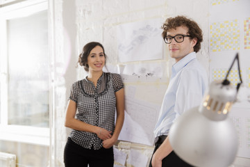 Portrait of two young architects in office