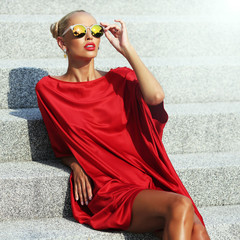 Fashion portrait of elegant stylish girl in a red dress and sung