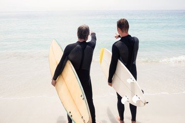 Father and son with surfboard and pointing at distance