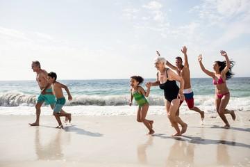 Happy family running on beach