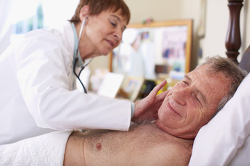 Doctor examining senior man at home