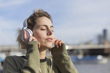 UK, London, woman listening music at River Thames