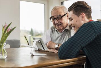 Happy senior man and his grandson looking at mini tablet