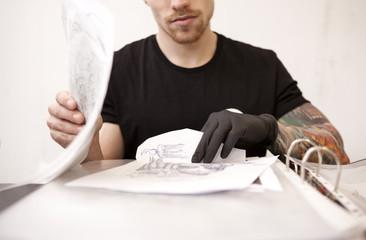 Tattooist with drafts in his tattoo studio