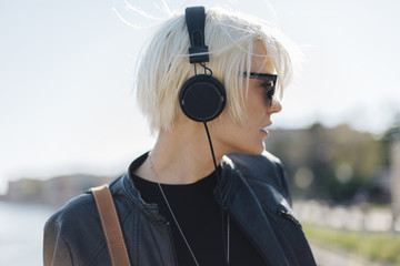 Profile of blond woman wearing sunglasses listening music with headphones