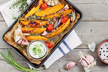 Baked sweet potatoes with tomatoes, herbs and cream fresh dip.Superfoods concept.Selective focus