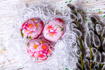 Easter eggs with pussy willow on light background