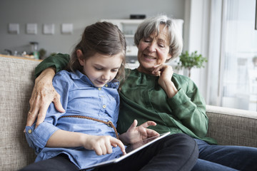 Grandmother and her granddaughter sitting together on the couch with digital tablet
