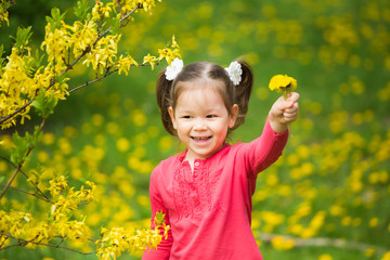 Portrait of funy little girl with yellow dandelions in hand. Beautiful smiling child playing with flowers on spring day in meadow. Baby holding bouquet of spring flowers at green grass background.