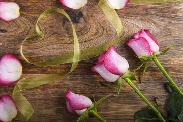 three white and pink rose with water drops, green ribbon heart and petals on wood