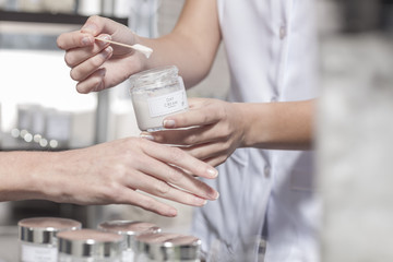 Cosmetician applying day cream on client's hand