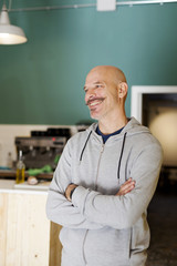 Mature man standing in restaurant with arms crossed, smiling