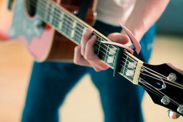 Gitarre spielen, Westerngitarre, Gitarrenhals mit Kapodaster, Person zu sehen