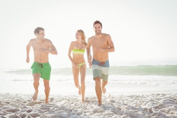 Happy friends running on the beach