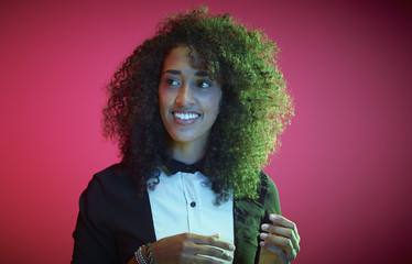 Portrait of smiling young woman with Afro in front of red background watching something