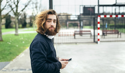 Portrait of bearded young man with smartphone and headphones