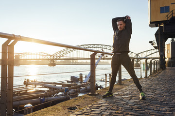 Germany, Cologne, Young man worming up for workout
