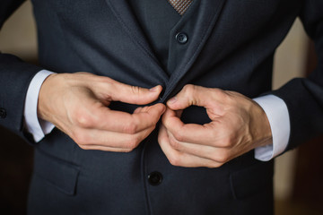 correct button on jacket, hands close-up, dressing, man's style, correcting sleeves,  preparing for the wedding