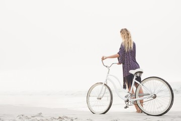 Pretty blonde woman walking next to her bicycle