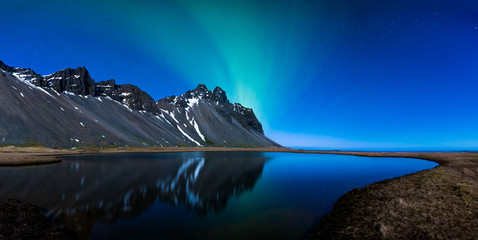 Wall Mural - Panoramic of Northern lights and mountains behind a lake
