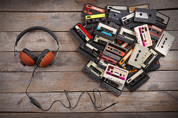Group of audio cassettes with headphones on wooden table background
