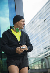 Germany, Baden-Wuerttemberg, Mannheim, athletic mature man with headphones and smartphone