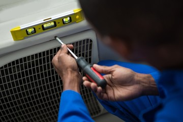 Handyman testing air conditioner with screwdriver