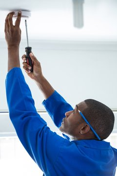 Handyman fixing the smoke detector with screwdriver