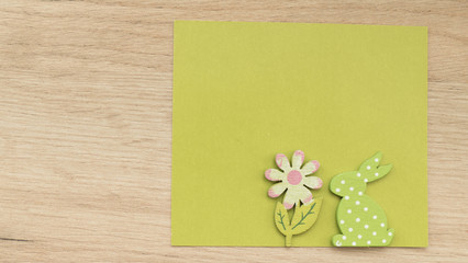 Easter rabbit with flower on green paper sheet
