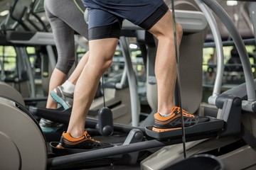 Woman and man exercising on the elliptical machine