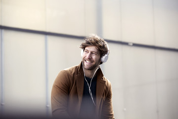Smiling young man listening music with headphones at backlight