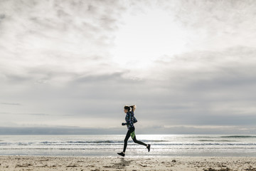 Spain, Tarragona, Woman running on a beach in winter