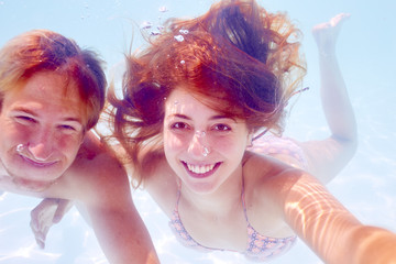 South Africa, Capetown, Young couple swimming in pool underwater