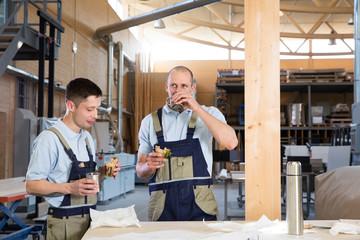 Craftsman in workshop having breakfast break