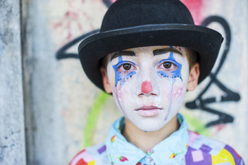 Portrait of sad boy rouged as a clown