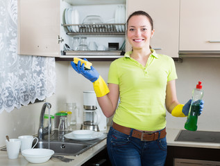 Happy young housewife washing dishes