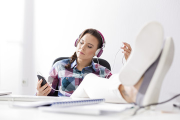Relaxed young woman with headphones at desk
