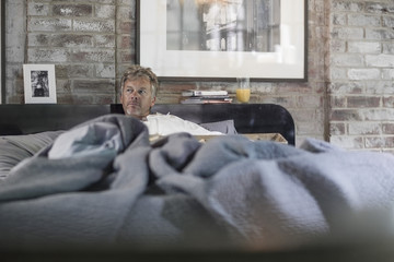 Portrait of pensive man in bed