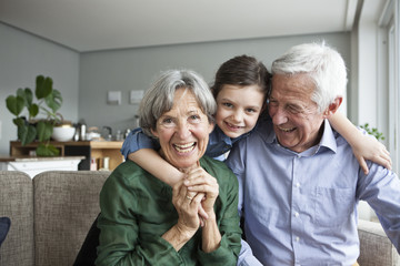 Family portrait of grandparents and their granddaughter at home