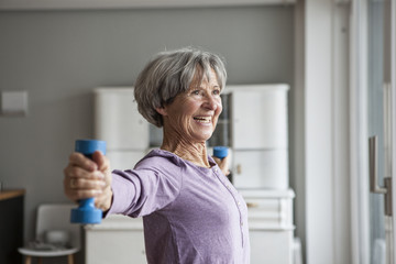 Portrait of happy senior woman doing fitness exercise with dumbbells at home