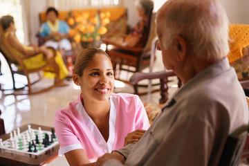 Hospice Nurse Helping Elderly Man On Wheelchair